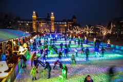 许多人民在冬天滑冰的溜冰场在Rijksmuseum前面的晚上,一个普遍的旅游目的地滑冰在阿姆斯特丹 免版税库存图片