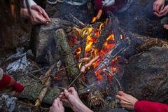 许多人民油煎香肠和薄煎饼在火在一顿野餐期间在冬天 库存图片