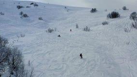 许多人freeriding在小山,蓬松新鲜的雪,在4k的空中英尺长度下 股票录像