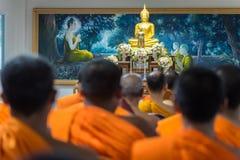 许多修士坐佛教仪式,在菩萨前面 库存照片