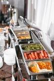 许多冲击激昂的盘准备好服务 在旅馆承办酒席自助餐,有温暖的饭食的金属容器的早餐 免版税图库摄影