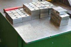 许多发光的金属,电烙与操练的孔、金属制品工具和工业夹子的长方形空白在t的机器人选材台上 免版税库存图片