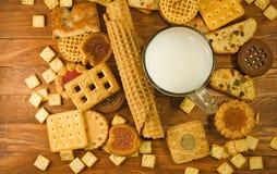 许多可口曲奇饼和牛奶在桌特写镜头 免版税库存照片