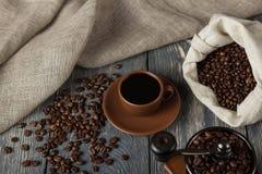 许多咖啡豆,有饮料的,手动压榨机杯,在灰色背景 库存图片
