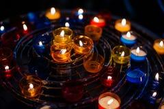 许多在五颜六色的烛台的燃烧的蜡烛在教会里 免版税库存照片