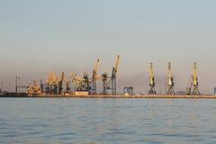 许多在口岸的大起重机剪影在日落金黄光  马里乌波尔,乌克兰 免版税库存图片