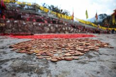 许多在地板上的硬币在一个宗教地方 库存照片