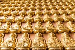 许多在墙壁上的小金黄菩萨雕象在中国寺庙 免版税图库摄影