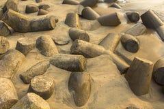 许多在湿黄沙外面的灰色具体tetrapods棍子 海啸障碍 免版税库存照片