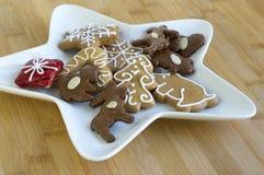 许多在白色板材,轻的姜饼的圣诞节曲奇饼黑暗和,星形状盘,竹木背景 免版税库存照片