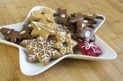 许多在白色板材,轻的姜饼的圣诞节曲奇饼黑暗和,星形状盘,竹木背景 免版税图库摄影