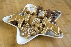 许多在白色板材,轻的姜饼的圣诞节曲奇饼黑暗和,星形状盘,竹木背景 库存照片