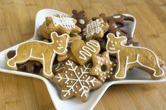 许多在白色板材,轻的姜饼的圣诞节曲奇饼黑暗和,星形状盘,竹木背景 图库摄影
