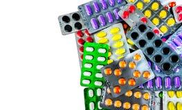 许多在白色背景隔绝的片剂药片 在天线罩包装的黄色,紫色,黑,橙色,桃红色,绿色片剂药片 免版税图库摄影