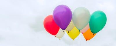 许多在蓝天的五颜六色的爱的气球,概念在夏天和华伦泰,婚姻的蜜月-全景横幅 免版税图库摄影