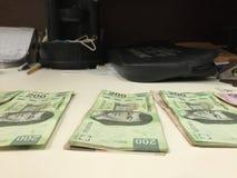 许多墨西哥比索票据分布了和在一张米黄色的书桌上的传播 图库摄影