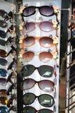 许多太阳样式遮蔽在显示的玻璃 免版税库存图片