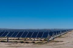 许多太阳电池板在有蓝天的沙漠 免版税库存照片