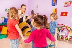 许多孩子在幼儿园拍有老师的手 免版税库存照片