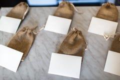 许多小棕色袋子织品和白色卡片 免版税库存照片