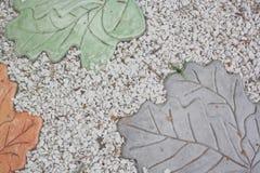 许多小白色石头和被仿造的瓦片类似叶子并且是绿色和灰色和桔子 免版税库存照片