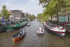 许多小船在运河在春天乘坐在阿姆斯特丹在一个晴天 免版税库存照片