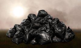 许多山废垃圾袋塑料的黑色小山,从废物的污染,环境损害背景污染发布  免版税图库摄影