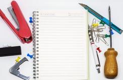 许多工具和空白的笔记 免版税库存照片