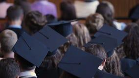 许多年轻人和妇女坐在大学礼堂的学术盖帽的 股票视频