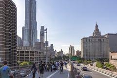 许多徒步旅行者和骑自行车者在布鲁克林大桥初在纽约附近,美国政府大厦  免版税库存图片