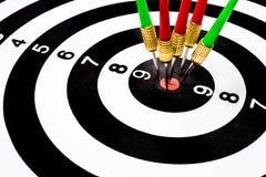 许多投掷击中在掷镖的圆靶的目标中心的箭头 库存图片
