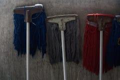 许多拖把用倾斜对墙壁的不同的颜色 免版税库存图片
