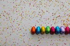 许多排列了在白色背景和五颜六色的五彩纸屑的色的巧克力复活节彩蛋 免版税库存图片
