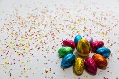 许多排列了在白色背景和五颜六色的五彩纸屑的色的巧克力复活节彩蛋 库存图片