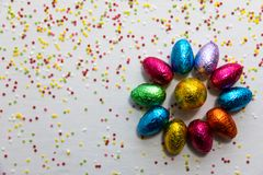 许多排列了在白色背景和五颜六色的五彩纸屑的色的巧克力复活节彩蛋 图库摄影