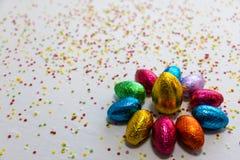 许多排列了在白色背景和五颜六色的五彩纸屑的色的巧克力复活节彩蛋 库存照片