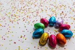 许多排列了在白色背景和五颜六色的五彩纸屑的色的巧克力复活节彩蛋 免版税库存照片
