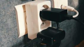 许多接通壁装电源插座 在壁装电源插座的适配器充电器 股票录像