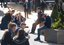 许多放松在公园的办公室人在伦敦市,伦敦 免版税库存照片