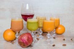 许多新鲜的汁液混合菜和果子,在灰色桌上的健康饮料 免版税图库摄影