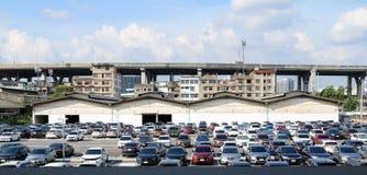 许多汽车停放在与车库大厦的室外停车场和高楼、高速公路和天空蔚蓝 库存图片
