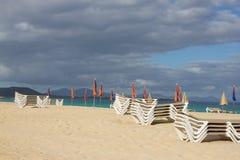 许多沙滩伞和椅子在天际排行 在天空背景的闭合的海滩遮阳伞 海湾回归线 完善的海边 库存照片