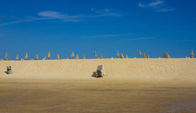 许多沙滩伞和椅子在天际排行 在天空背景的闭合的海滩遮阳伞 海湾回归线 完善的海边 免版税库存照片