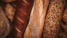 许多混合了被烘烤的面包和卷在土气木桌上 库存图片