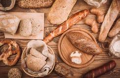 许多混合了被烘烤的面包和卷在土气木桌上 库存照片