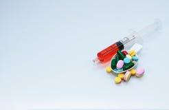 许多片剂和药片在匙子和液体在注射器服麻醉剂 图库摄影