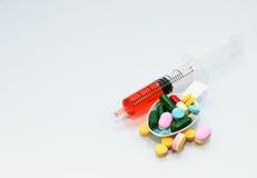 许多片剂和药片在匙子和液体在注射器服麻醉剂 免版税图库摄影