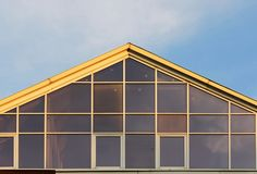 许多玻璃大窗口在蓝天背景的房子里 免版税图库摄影