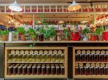 许多玻璃瓶子用果酱和柠檬水在明亮的咖啡馆里面与五颜六色的内部 库存图片