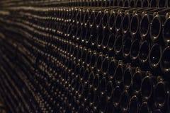 许多瓶香槟在黑暗的葡萄酒库在甚而行在一盏黄色灯的光下 免版税库存照片